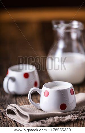 Milk. Cove or goat milk. Pouring milk into glass.