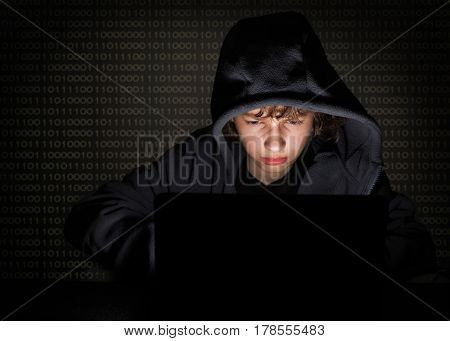 Teenager hacker at the computer on a digital background