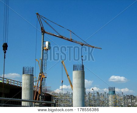 large cranes on the construction site of the bridge construction