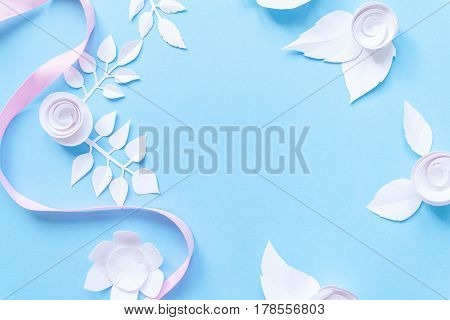 Frame With White Paper Flowers And Pink Ribbon On Blue Background. Cut From Paper.