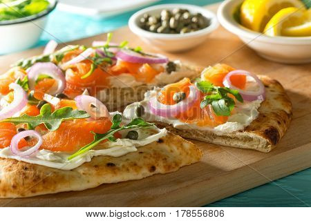 A delicious home made smoked salmon pizza with cream cheese red onion capers and baby arugula.
