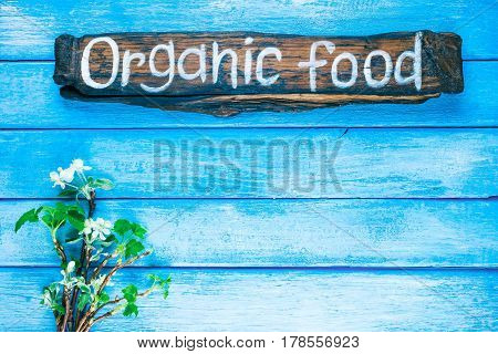 Background of narrow wood planks painted in blue. Bunch of blooming apple tree and young black current twigs. Wood signboard with text 'Organic food' as title bar