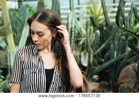 Young fashionable caucasian woman with long hair wearing hat and striped blouse basking in sunlight inside greenhouse near agave and cactus plants