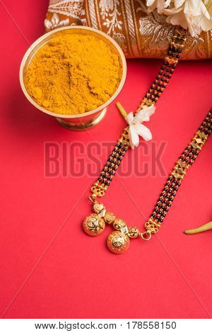 close-up photo of a Mangalsutra or necklace to worn by a married hindu women, with traditional saree or paithani with huldi kumkum and mogra flowers or Jasminum sambac garland