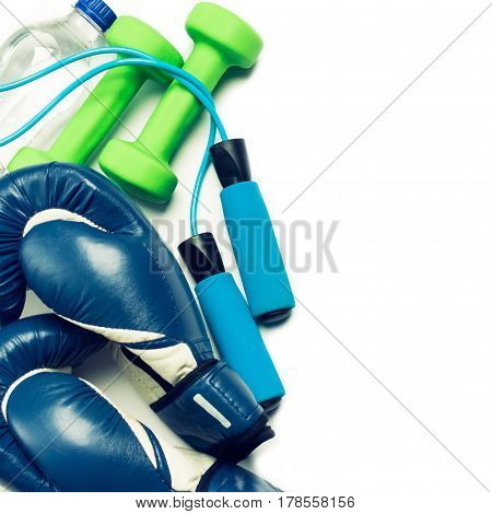 Fitness concept - boxing glove dumbbells skipping rope and bottle on the white background