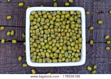 Mung beans in a ceramic bowl on wooden table