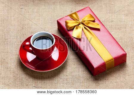 Photo Of Cup Of Coffee And Cute Wrapped Gift On The Wonderful Brown Fabric Background