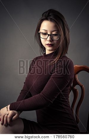 portrait pensive young girl sitting on chair