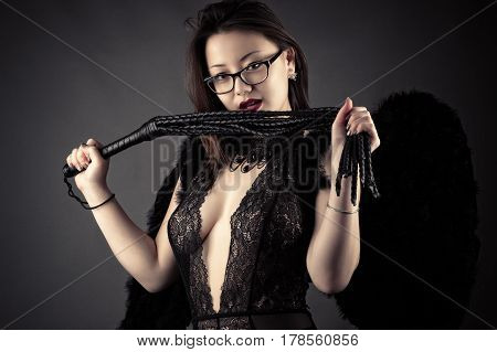 young Korean girl with whip in hands with black wings