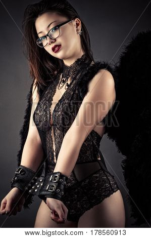 luxurious beautiful woman in handcuffs and black wings