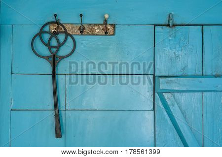 Black plastic carpet beater hanging on hook on blue wall