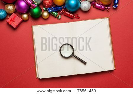 Notebook, Magnifying Glass And Beautiful Christmas Decorations On The Wonderful Red Background
