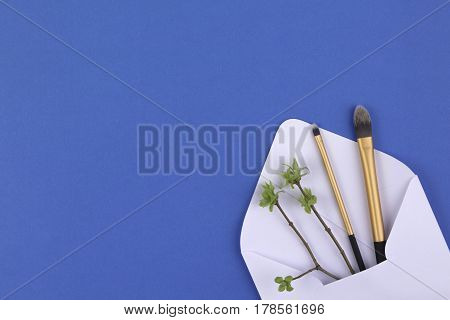 Make up brushes in white envelope with first spring gentle leaves and buds on small tree twigs. Top view
