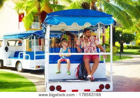 Happy Tourist Family Enjoying Vacation While Riding In Vehicle Through The Hotel Area. Transportatio