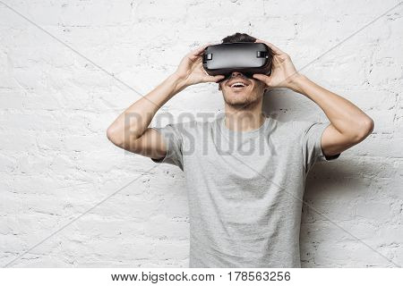 Hansome european male in gray t-shirt experiencing virtual reality using VR headset glasses. Young caucasian man wearing oculus or goggles playing video games standing against white brick wall