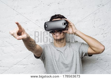 Smiling man using oculus rift headset experiencing virtual reality while playing video game. Young tattooed european male wearing 3d glasses pointing his finger as if interacting with something