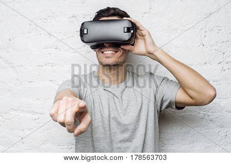 Young handsome caucasian man wearing 3d glasses pointing his fingers as if interacting with something. Smiling attractive man using VR headset experiencing virtual reality while playing video game