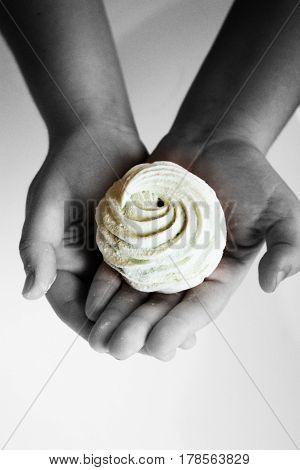 Marshmallow (zephyr) in woman's hand. zephyr in hands