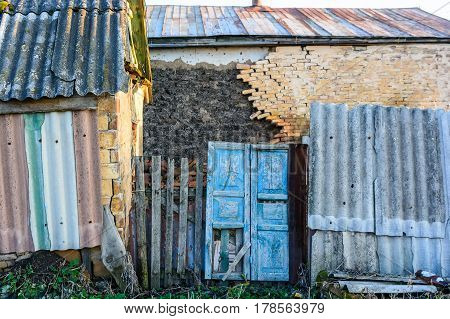 Exteriour of abandoned obsolete rustic house with damaged brick wall and blue door