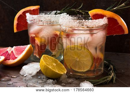 Nonalcoholic cocktail of fresh fruits: grapefruit, lime, rosemary. Concept of a healthy drink. Rusty metal background