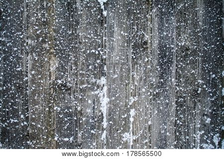 Old snow-covered boards, white snowflakes. Winter background