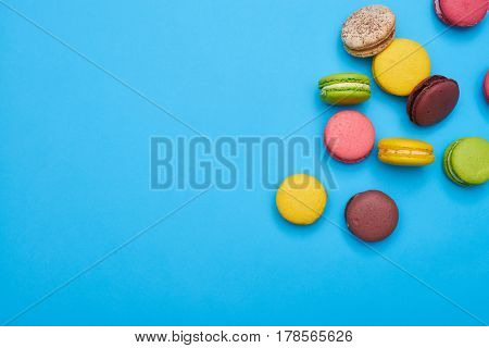 Some homemade macaroons scattered over blue flatlay