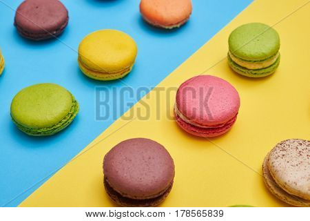 Several french cookies macaroons arranged on a blue flatlay. Different types of macaroons