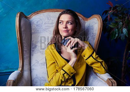 Close-up shot of a dreamy young woman holding phone in hands and looking at the window. FEmale in a yellow blouse sitting in an armchair. Looking sideward