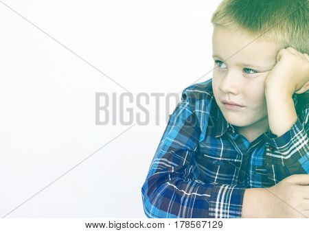 Young boy sitting and being serious