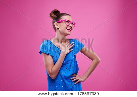 Mid shot of positive smiley girl with hand on chest looking sideways. Young woman in dotted dress smiling and posing over pink background