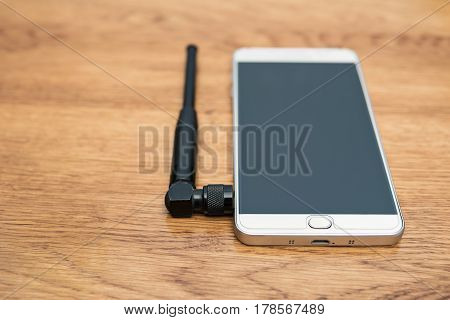 Big smartphone with a small antenna lying on a wooden table