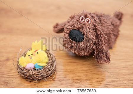 Toy nest with yellow chickens and Easter eggs next to a plush dog on a wooden table, blurry