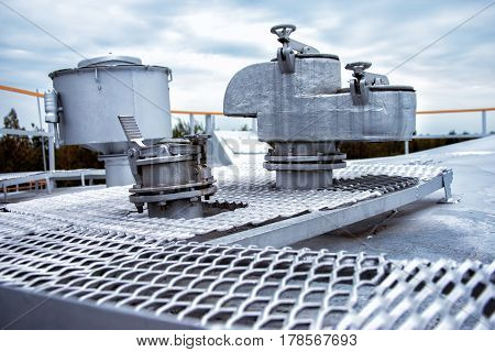 Large steel safety valve on the roof of the tank with gasoline
