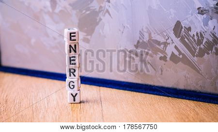 ENERGY cube letter in pile with solar silicon cell surface in background. Concept of renewable clean energy.
