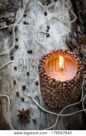 Burning Aromatic Coffee Candle And Coffee Beans On Aged Wood