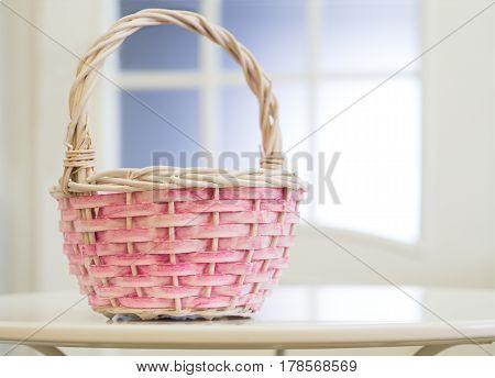 Wicker basket on white table on window background