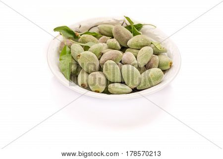 Fresh green unripe almonds in plate with pure white background