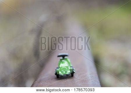 Green steel toy train in a blurred background conceptual photo