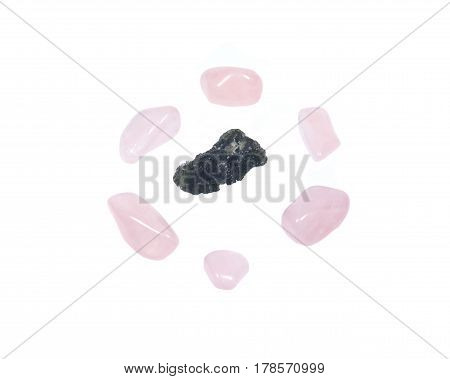 Moldavite - form of tektite found along the banks of the river Moldau in Czech republic, isolated on white background, surrounded by tumbled rose quartz pieces