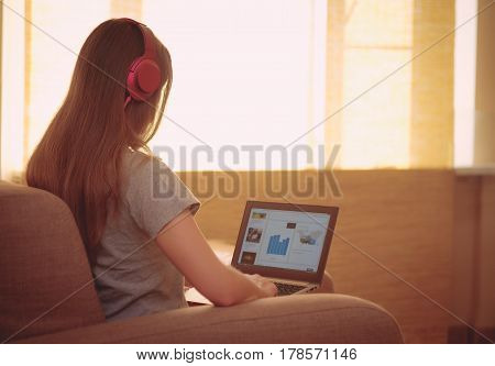 Happy woman with pink headphones listening to music and watching on notebook. Young woman sit backwards at home on a couch use laptop and enjoy the music with headphones near sunny window