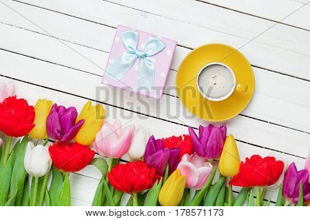 photo of cup of coffee cute gift and colorful tulips on the wonderful white wooden background
