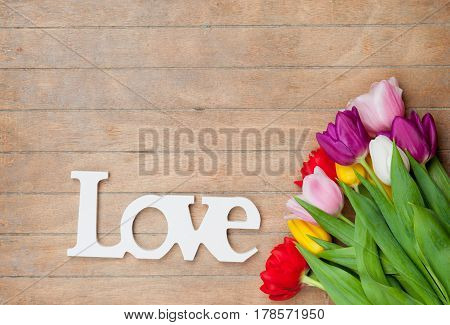 Photo Of Beautiful Bunch Of Colorful Tulips And Wooden Tablet  On The Wonderful Brown Wooden Backgro