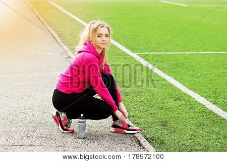 Young Beautiful Blonde Hair Fitness Girl Ties Shoelaces On The Stadium. Summer Sports Activity.