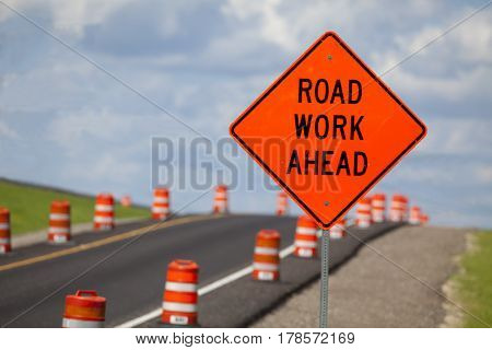 Road construction zone with orange warning sign.