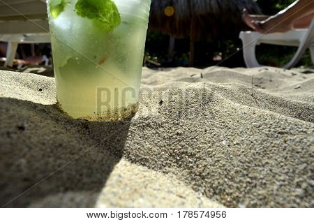 Cuban original mojito with peppermint leaves, ice and sugar in a plastic cup buried in the brown sand of  the beach, in background a beach bed with some feet enjoying the sun.