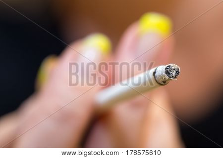 Cigarette in hand . The person is engaged in work