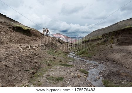 A Quechuan womn and her horse with a tourist passenger on the Pe