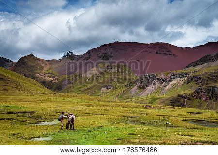 Peruvian country side in Ausangate, with a Quechuan and his horse in the distance