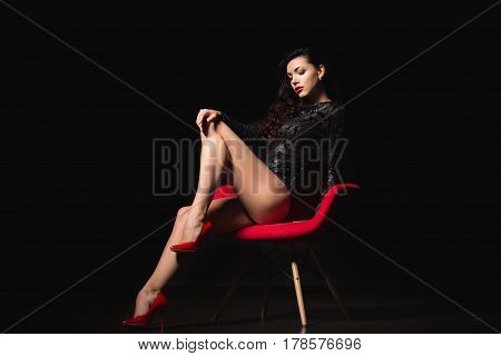 Fashion portrait. Perfect, sexy body and long legs of young woman wearing seductive lingerie posing in a sensual way in dark room by red modern chair.