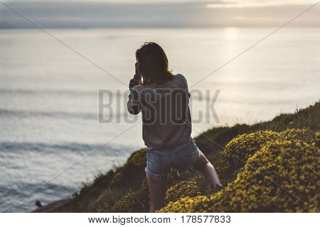 Clouds sky and sunlight sunset on horizon ocean. Silhouette person tourist traveler photographer making pictures seascape on vintage photo camera on background sunrise. Relax view mockup evening nature
